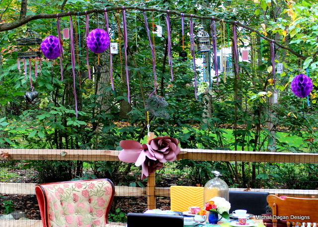 Ribbons, keys, cards, bird cages and tea pots hang from the tree above the table